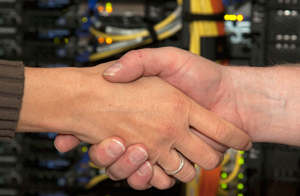 Engaging with UCAR: Handshake in front of supercomputer